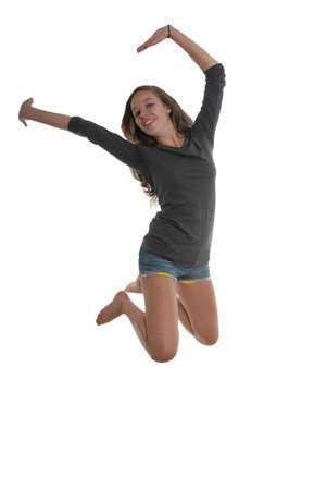 Cheerful happy graceful teenager girl jumping in the air with arms and feet behind head knees bent arched backwards wearing t-shirt, and shorts.