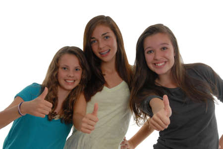 All thumbs up three teenager girls happy together as friends, showing approval. In studio on white background.