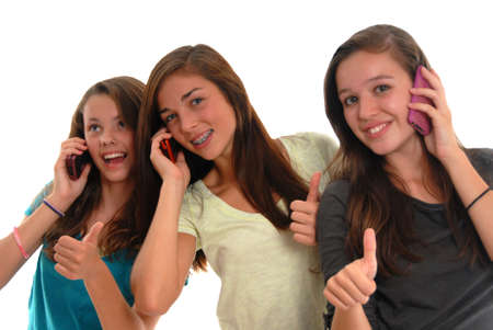 Three happy teenage girls smiling and thumbs up while talking on cell phones. Studio with white background. Stock Photo - 10756976