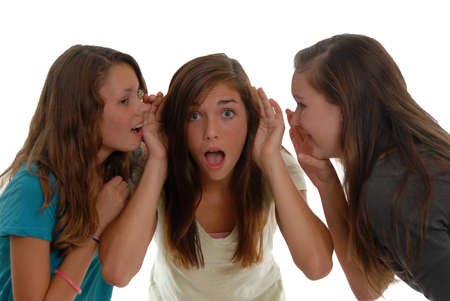 Two teenage girls whispering in both ears of another girl who is shocked at what she is hearing. The rumor mill is at work here. Stock Photo