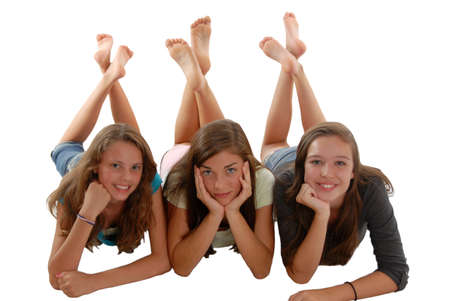 Three teenage girls laying on their stomach on the floor with chin in hands, and feet raised up and crossed behind them on white background in studio.