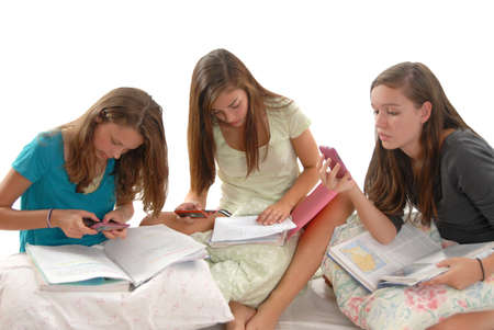 resourceful: Three teenage girls sitting on the floor with books on pillows using cell phones to help them surf information for there homework. White background in studio.  Stock Photo