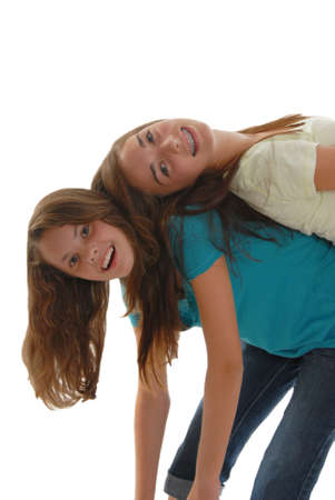 Two teenage girls horsing around having fun with one bent over and the other one laying back to back bending backwards