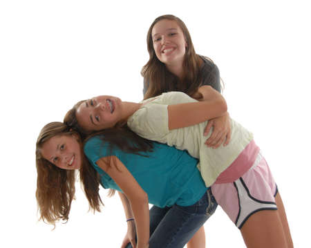 Three friendly teenage girls having fun. One girl bending over backwards laying on the back of another girl leaned forwards with yet another girl on looking.
