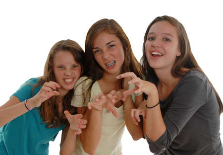 Three teenage girls posing like cats or tigers, gritting teeth, raised claws, and snarling like cat woman. Isolated on white background. In Studio