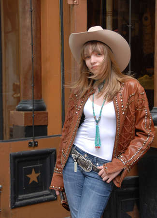 Young girl standing outside of a western style store with slight wind blowing blond hair across face wearing western cloths.