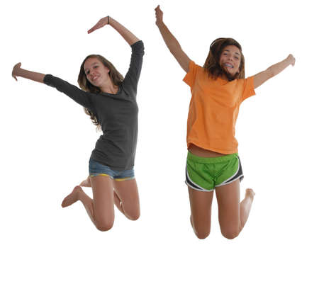knees bent: Two cheerful happy graceful teenager girls jumping in the air with arms and feet behind head knees bent arched backwards wearing t-shirt, and shorts.  Stock Photo