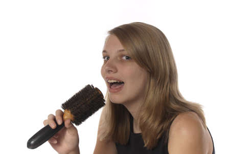 hair brush: Young teenage girl singing into her hair brush. Future singing star practices with an imitation microphone. Stock Photo