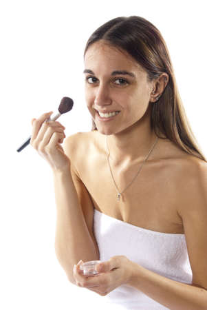 Pretty young woman applies make up, facial blush, cosmetics wrapped in towel. In studio on white background.