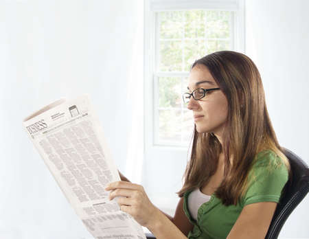 Young woman sitting in a chair reading business section of the newspaper in front of window.