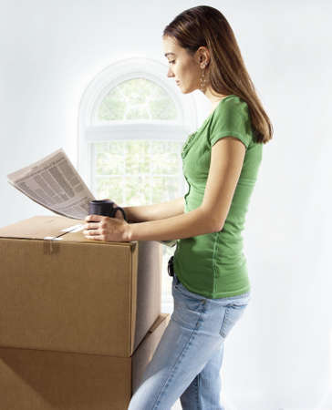 Young woman stops packing or unpacking from moving into home and takes a rest break, drinking coffee, and reading business section of news paper.