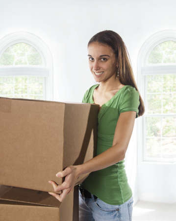 Young woman moving into a new home and is moving, taping and unpacking boxes. Soft backgorund.