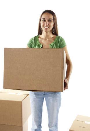 carga: Pretty ama de casa haciendo las maletas para mudarse a una nueva casa o acaba de mudarse y mover elementos almacenados en torno a diferentes habitaciones de la casa. Podría ser un trabajador en un almacén de cajas de mudanza. En el estudio sobre fondo blanco. Foto de archivo
