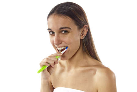 Pretty young women brushes her teeth wrapped in a towel looking into the camera. Portrait photo in studio on white background. photo