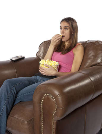 sits on a chair: Young woman sits in a leather chair relaxing and eating popcorn facing to left  This could be retro of the house wife at home watching a soap opera or movie night  Could also be someone watching a sports event on TV like football, baseball, basketball, or
