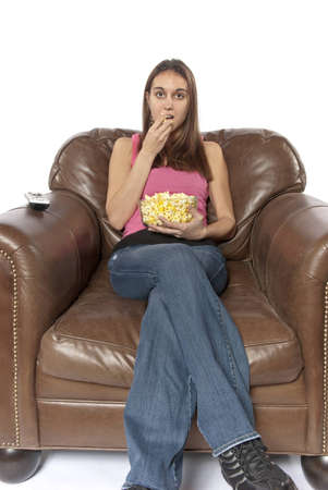 Young woman sits in a leather chair relaxing and eating popcorn facing forward  This could be retro of the house wife at home watching a soap opera or movie night  Could also be someone watching a sports event on TV like football, baseball, basketball, or photo