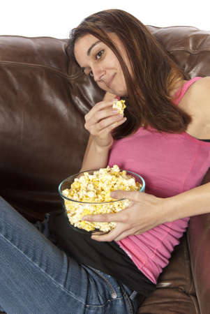 sits on a chair: Young woman sits in a leather chair relaxing and eating popcorn