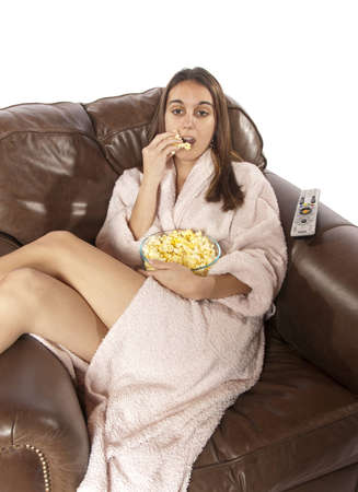 bowl of popcorn: Young woman sits in a leather chair in house coat relaxing and eating popcorn  Head laying on back of couch  This could be retro of the house wife at home watching a soap opera or movie night  Could also be someone watching a sports event on TV like footb