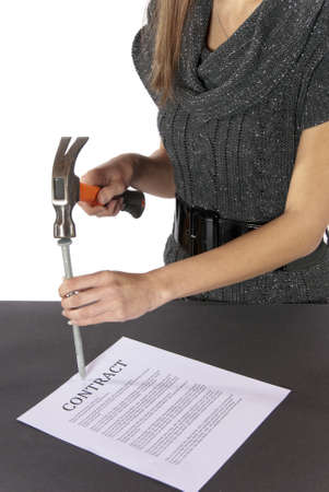 Metaphor businesswoman nails contract agreement  Partial view of nicely dressed businesswoman holding a hammer is putting a nail in the contract as if she has just nailed it  The contract isn