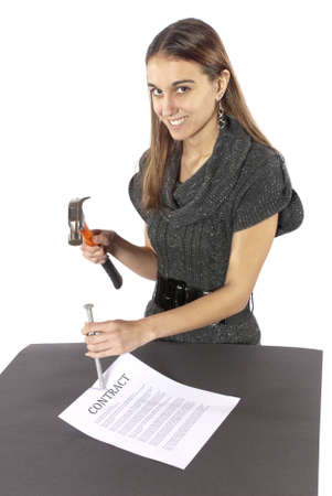Metaphor businesswoman nails contract agreement  Happy with paper flat on table  Nicely dressed businesswoman holding a hammer is putting a nail in the contract as if she has just nailed it  The contract isn