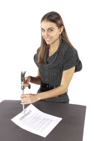 Metaphor businesswoman nails contract agreement  Happy with paper flat on table  Nicely dressed businesswoman holding a hammer is putting a nail in the contract as if she has just nailed it  The contract in Stok Fotoğraf