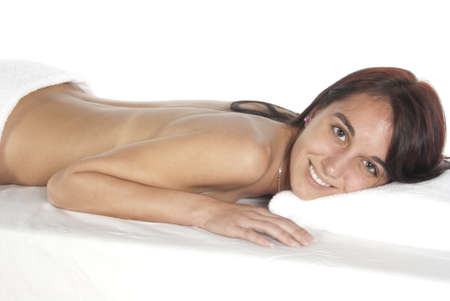 Smiling eyes open. Spa therapy pretty young brunette woman, partial nude laying on covered table. In studio on white background.