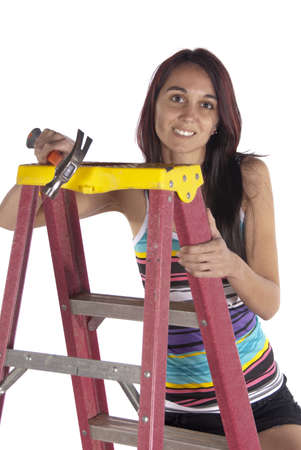 Pretty young brunette is climbing a ladder
