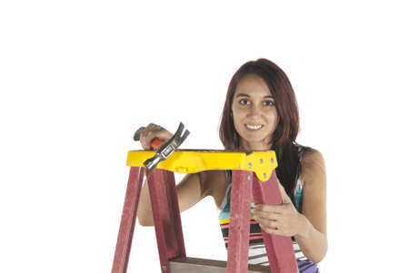 Young woman casual dressed working with tools using a step ladder to help her higher  In studio on white background