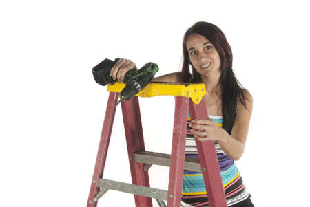 Young woman casual dressed working with drill using a step ladder to help her higher  In studio on white background  Stock Photo