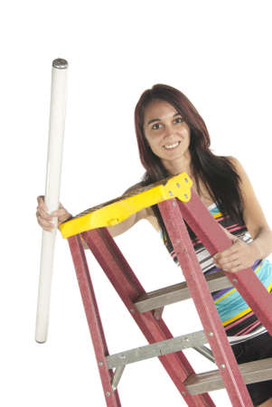 Young woman climbing a step ladder and attempting to install a florescent bulb  Casual dressed in studio on white background Stock Photo - 17446051