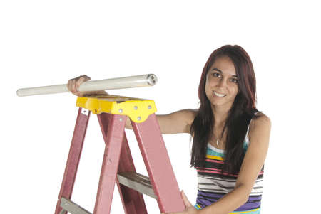 Young woman climbing a step ladder and attempting to install a florescent bulb  Casual dressed in studio on white background  Stok Fotoğraf