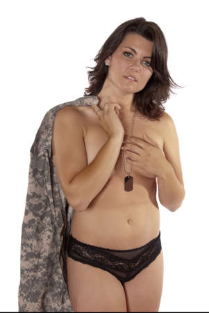 woman nude standing: Sexy young woman holding part of an American soldiers uniform. Standing nude wearing only panties. Patriotic,