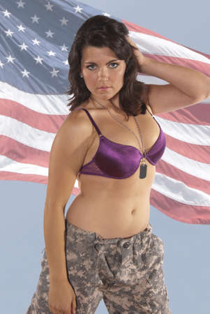 Sexy young woman in front of a flag, wearing part of an American soldiers uniform pants, dog tag, and a bra. Patriotic, for the holidays fourth of July, independence day, flag day,  photo