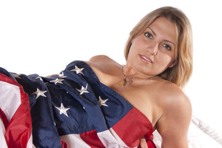 Sexy young woman implied nude wrapped American Flag looking into the camera seductively  Patriotic, for the holidays fourth of July, labor day, independence day, new years day, flag day, veterans day