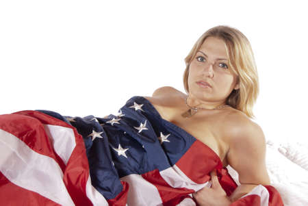 Sexy young woman implied nude wrapped American Flag looking into the camera seductively  Pattic, for the holidays fourth of July, labor day, independence day, new years day, flag day, veterans day Stock Photo - 17992546