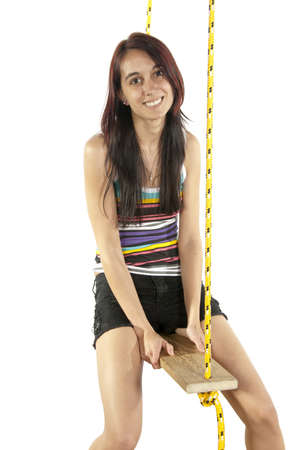 Pretty young brunette happily swings on a swing in casual attire Stok Fotoğraf