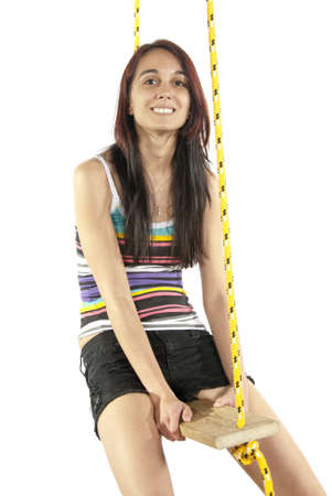 Pretty young brunette happily swings on a swing in casual attire head upward  In studio on white background