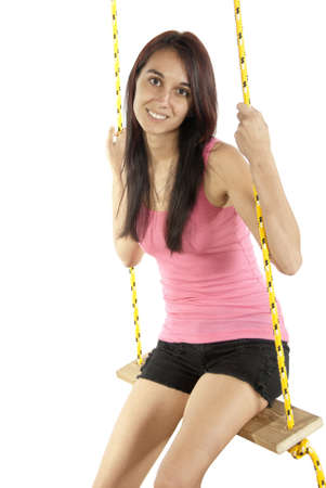 Pretty young brunette happily swings on a swing in casual attire  In studio on white background