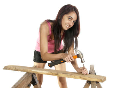 Young do it yourself female woodworker casual dressed working with hammer putting a nail into a piece of wood on a set of saw horses  In studio on white background
