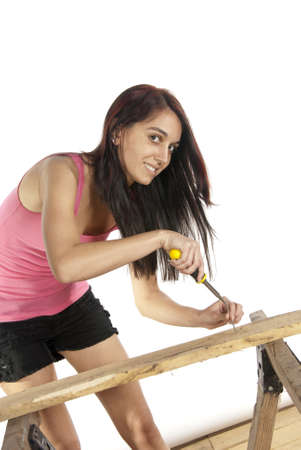 Young do it yourself female woodworker casual dressed working with a screwdriver putting a screw into a piece of wood on a set of saw horses  In studio on white background