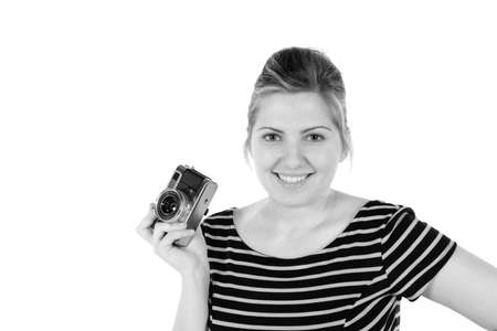 Retro black and white monochrome of beautiful young blond woman holding an antique camera. Hair teased up in bun. Photo in studio on white background and in Black and white.