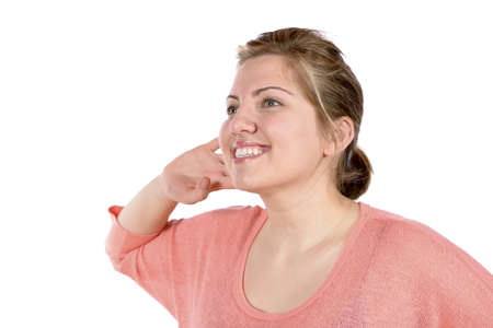 Woman listening with her hand up to her ear  Making gesture that she is expecting a sound from someone or something   In studio on white background Stock Photo