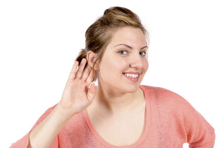 Woman listening with her hand up to her ear  Making gesture that she is expecting a sound from someone or something   In studio on white background Stok Fotoğraf