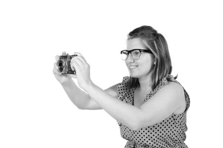 Retro black and white monochrome of beautiful young blond woman holding an antique camera  Hair teased up in bun  Photo in studio on white background and in Black and white