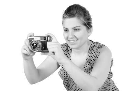 Retro black and white monochrome of beautiful young blond woman holding an antique camera