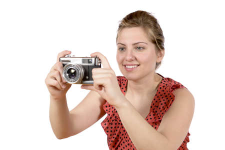 Retro of beautiful young blond woman holding an antique camera  Hair teased up in bun  Photo in studio on white background