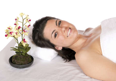 Spa therapy for happy pretty young brunette woman, wrapped in towel enjoying aroma therapy laying on massage table  In studio on white background
