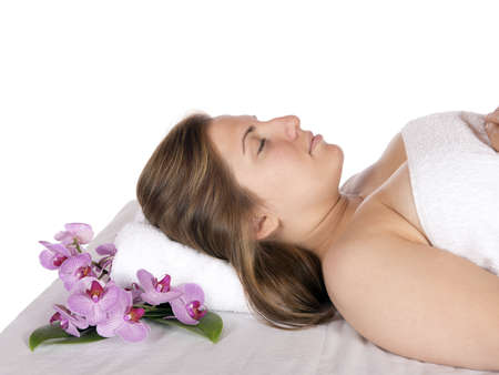 Spa therapy for happy pretty young blonde woman, wrapped in towel enjoying aroma therapy laying on massage table  In studio on white background