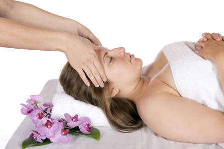 Spa therapy getting a head massage by technician masseuse for happy pretty young blonde woman, wrapped in towel while enjoying aroma therapy laying on massage table  In studio on white background
