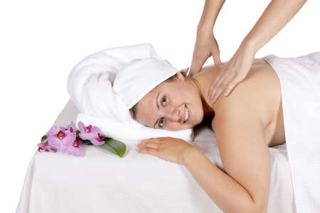 Spa therapy getting a back and shoulders massage by technician masseuse for happy pretty young blonde woman, wrapped in towel while enjoying aroma therapy laying on massage table  In studio on white background